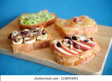 Toast party on wooden tray – avocado salt  pepper ,Apple  peanut butter almonds raisins, banana dark chocolate, Peach cinnamon  cream cheese rose, Isolated on wooden background. Healthy toast, healthy