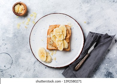 Toast with peanut butter, banana slices, honey and almond flakes on old gray concrete background. Top view.