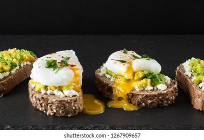 Toast with poached eggs, avocado on black background