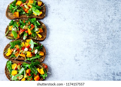 Toast with pumpkin and arugula. Open sandwiches with pumpkin. Healthy vegan toasts with greens and pumpkin. Autumnal snack. Bruschetta with arugula and pumpkin.