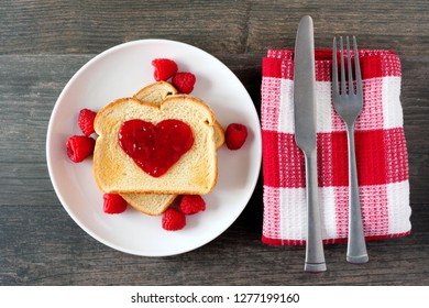 Toast with raspberry jam in shape of heart. Top view table setting over a dark wood background. Love concept.