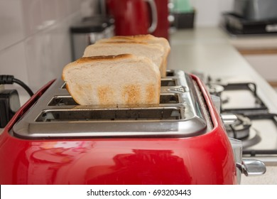 toast in a red toaster on kitchen work top.