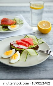 Toast sandwich with Salmon, Avocado,eggs and cucumber on plate on a table. healthy easy food