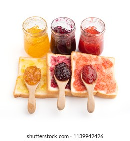 Toast sandwiches with strawberry, orange and blueberries jam isolated on white background, top view