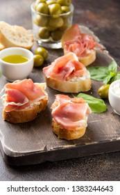 Toast with serrano ham (jamon, prosciutto crudo, hamon), traditional Italian antipasti. Delicious snack with bread, cream cheese, olives. Health food, appetizer for wine, bruschetta