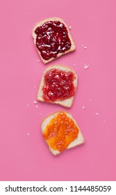 Toast slices with fruit jam on a pink background viewed from above. Selection of bread slices with fruit marmalade. Top view