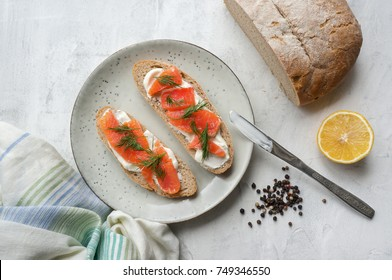 Toast with smoked salmon, cream cheese and dill on rustic plate. White concrete table. Scandinavian food. Natural source of Omega-3. Top view.