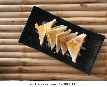Toast with sweetened condensed milk on bamboo table.