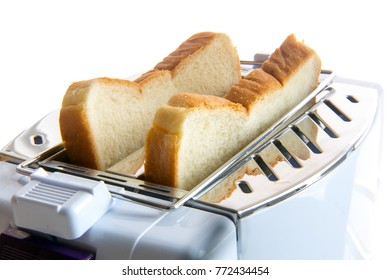 Toast in a toaster. Fried toast slices inside the toaster. A close-up view of pastries in a toasting device.