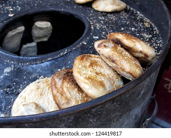 Toasted bao buns lined up on kettle with several more cooking in a Chinese street market