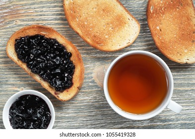Toasted bread with blueberry jam and a cup of tea on the old wooden table, top view