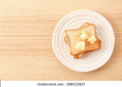 Toasted bread with butter curls on plate, top view