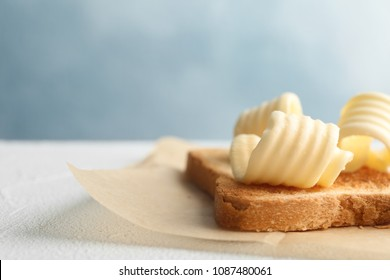 Toasted bread with fresh butter curls on table, closeup