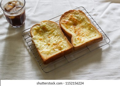 Toasted bread with garlic and cheese, glass of cold iced coffee in cloth background.