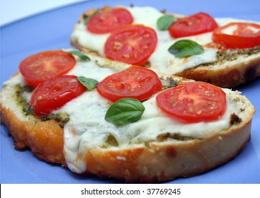 Toasted Bread Slices with pesto, tomato, basil and melted cheese