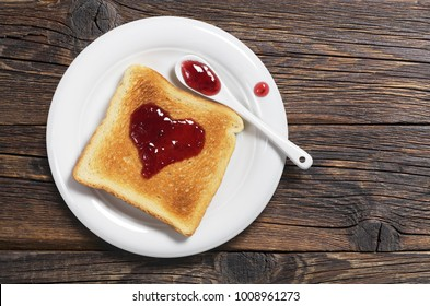 Toasted bread with strawberry jam in the shape of heart in plate on old wooden table, top view
