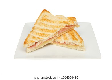 Toasted cheese and ham sandwich on a plate isolated against white