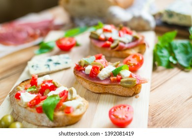 Toasted ciabatta, a cheese sandwich with mold, tomatoes, basil on a wooden background.