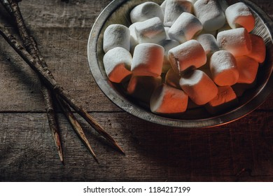 Toasted marshmallow ingredients with sticks by the campfire light