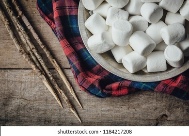 Toasted marshmallow ingredients with sticks and flannel shirt overhead view
