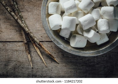 Toasted marshmallow ingredients with sticks on wooden table overhead view