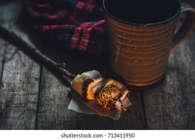 Toasted marshmallows and a mug in campfire light
