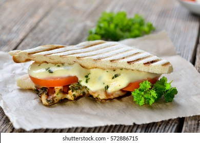 Toasted panini with grilled herb chicken breast fillet, melted mozzarella on tomato slices served on sandwich paper on a wooden table