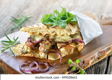 Toasted panini with grilled rosemary chicken breast fillet, melted mozzarella and roasted onion rings served on a wooden board