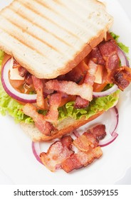 Toasted sandwich with fried bacon, onion and lettuce