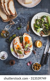 A Toasted sandwich with smoked salmon and fried eggs and variety cheese cutting board with bowl olives and green leaves salad from above a blue rustic table. Country simple mediterranean food .