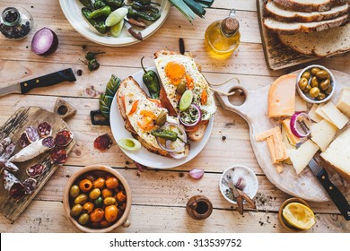A Toasted sandwich with smoked salmon and fried eggs and variety cheese cutting board with bowl olives and green leaves salad from above a wooden table. Country simple mediterranean food.