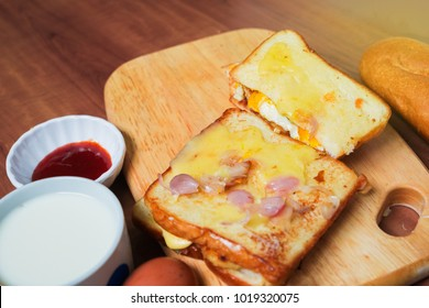Toasted sandwich with sunny side down eggs filled with meat,cheese, and mozzarella. Dishes ready to be served.