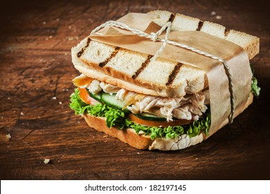 Toasted shredded chicken breast and salad sandwich served on a rustic wooden table wrapped in a brown paper wrapper tied with string with vignetting and copyspace