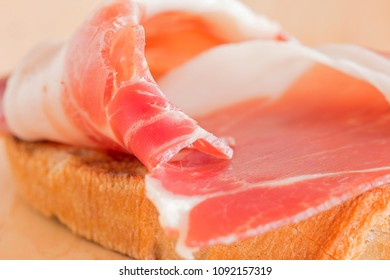 A toasted slice of bread with a slice of ham.