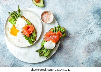 Toasted sourdough bread with grilled asparagus, salmon, avocado and poached eggs. View from above with copy space