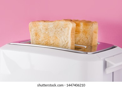 Toasted toast bread in white toaster on pink background
