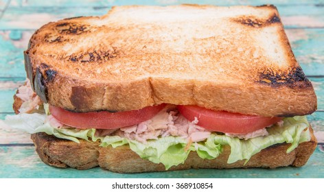 Toasted tuna sandwich with salad and slices tomatoes over wooden background