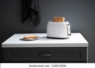 Toaster with bread slices on kitchen table