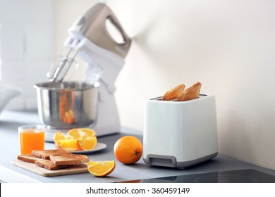 Toaster with mixer and oranges on a light kitchen table