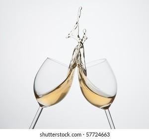 Toasting gesture two  white wine glasses with big splash