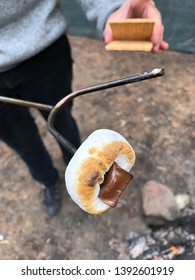 Toasting marshmallows and making s'mores over campfire