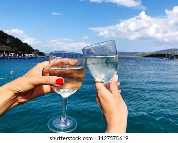 toasting wine glasses against sea