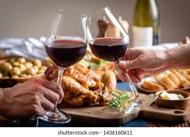 toasting with wine glasses in front of chicken dinner