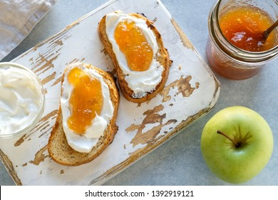 Toasts with apple jam, ricotta (cream cheese), served on white wooden rustic cutting board. Apple jam in a glass jar. Summer breakfast. Light blue stone background. Top view.