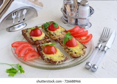 Toasts with aubergine, cheese and tomato on a glass plate.