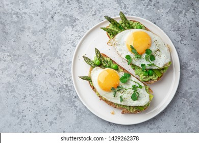 toasts with avocado, asparagus and fried egg on white plate, top view, grey background,