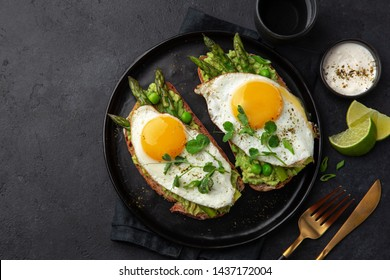 toasts with avocado, asparagus and fried egg on black plate, top view, dark background, copy space