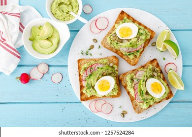 Toasts with avocado guacamole, fresh radish, boiled egg, chia and pumpkin seeds. Diet breakfast. Delicious and healthy plant-based food. Flat lay. Top view
