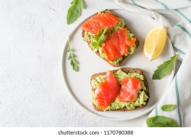 Toasts with avocado and salmon on plate over white background
