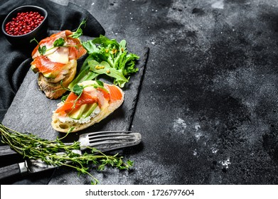 Toasts with avocado and smoked salmon. Black background. Top view. Copy space